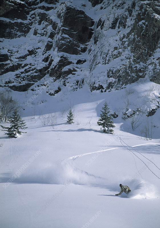 Snowboarder turning in powder snow
