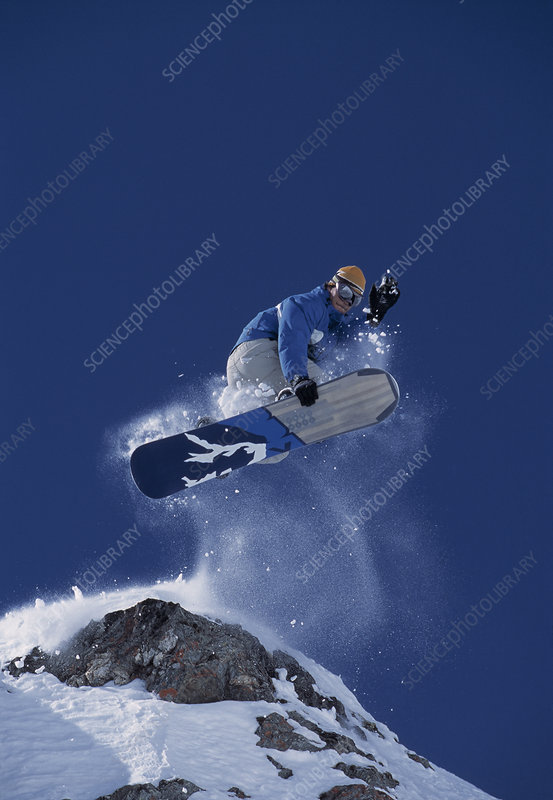 Snowboarder jumping off a rock