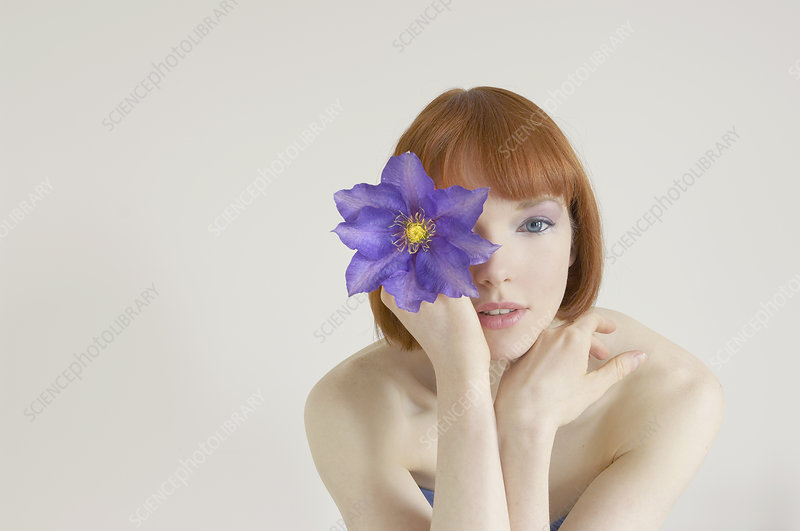 woman holding flower in front of eye