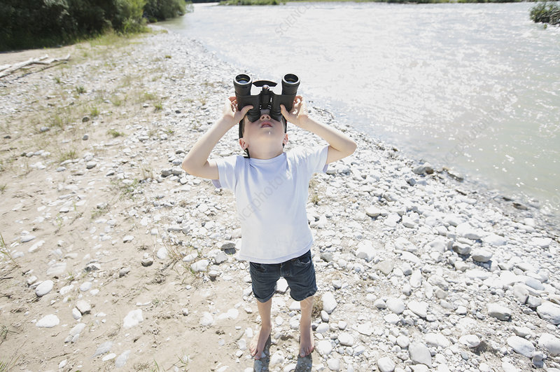 boy looking through field glasses