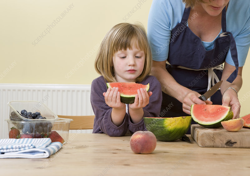 girl and mother with watermelon slices