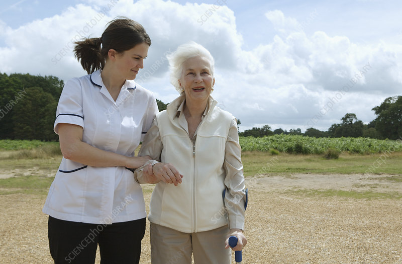 Elderly woman being supported by nurse