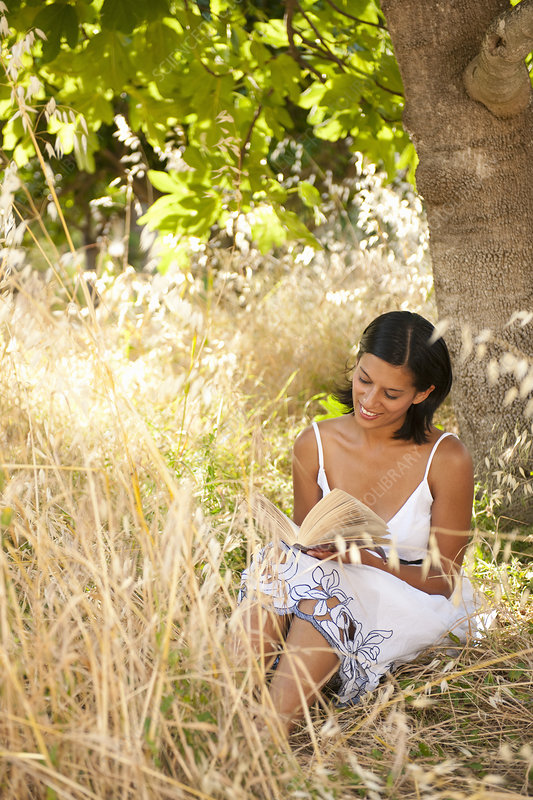 Young Woman Reading Book Under Tree
