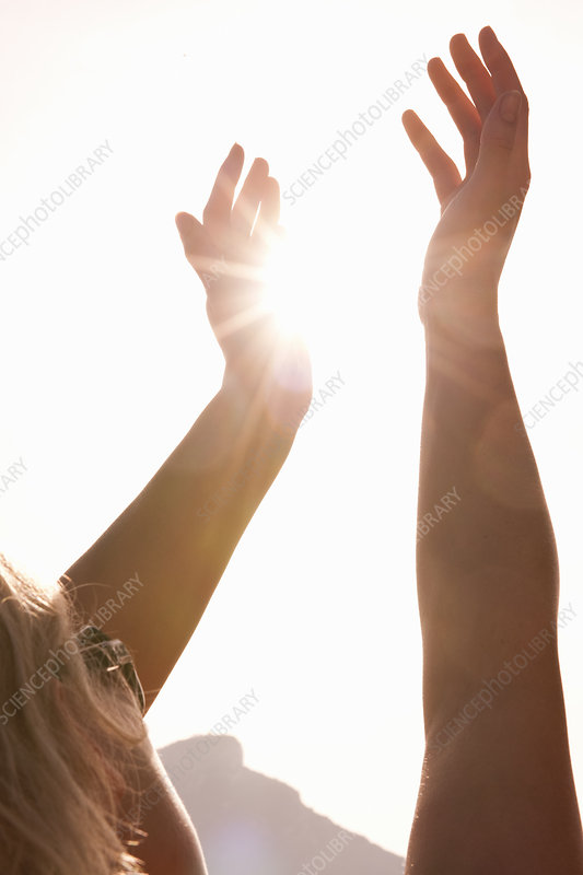 Woman Holding Arms Up To Sun