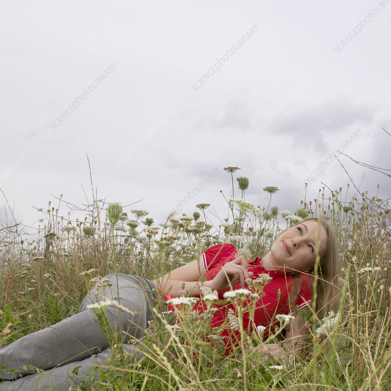 Young woman lying in high grass and flowe