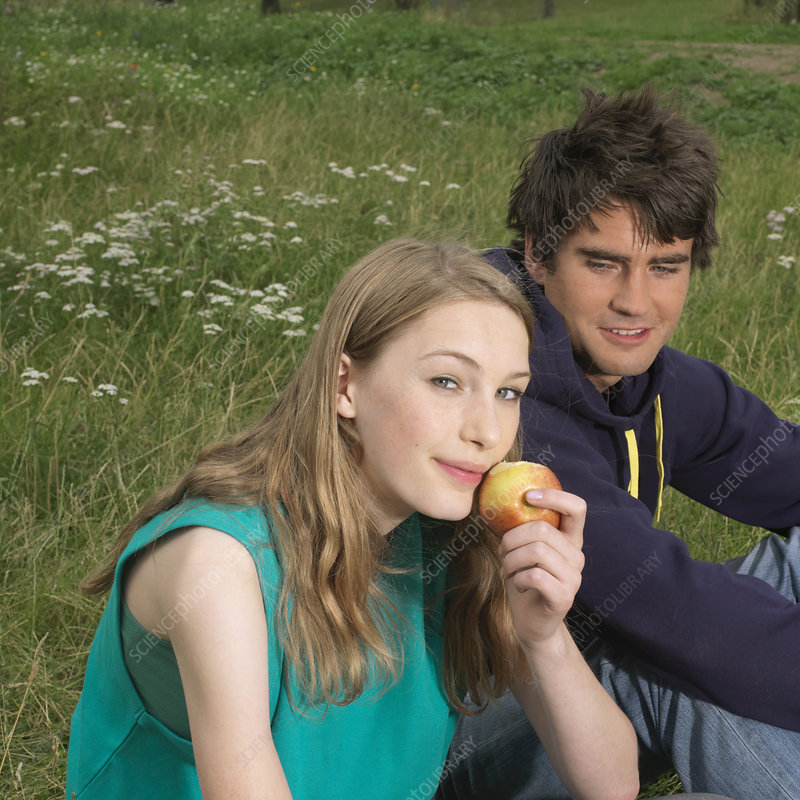 Young woman and man with an apple