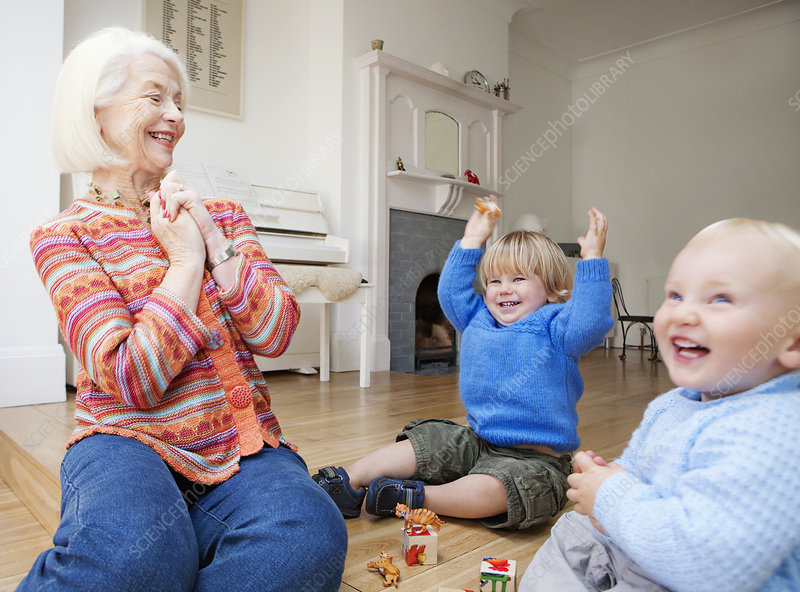 A grandmother playing with two toddlers