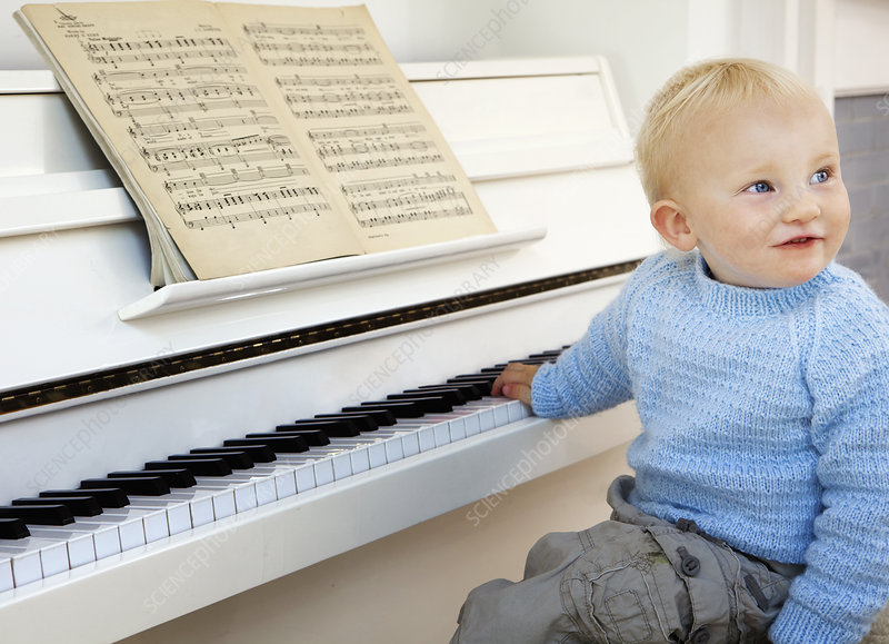 A boy toddler sitting at the piano