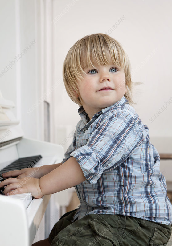 A boy toddler sitting at a piano
