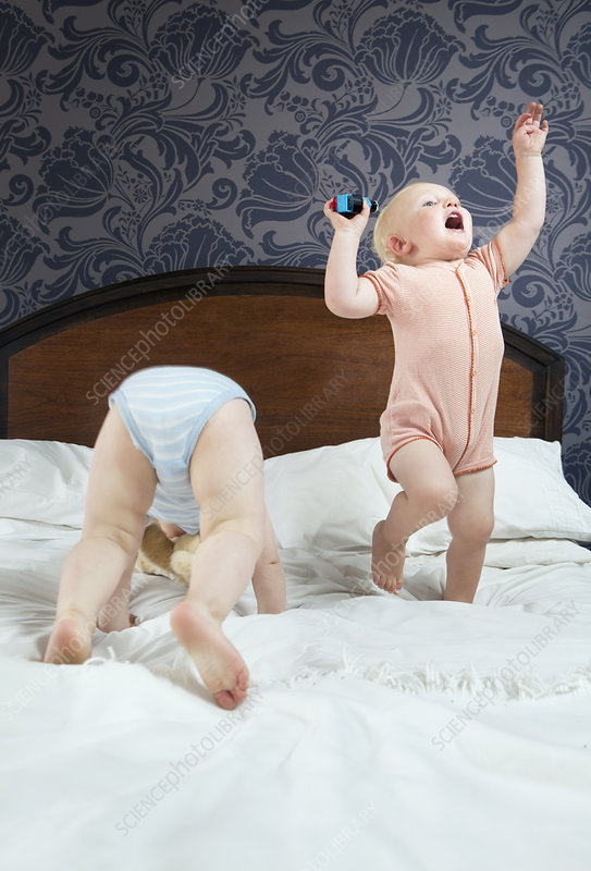 Two baby boys play on a bed