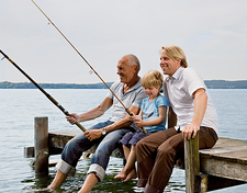 boy fishing with grandfather, father