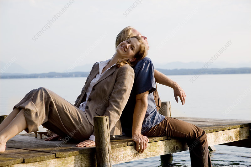 woman and man sitting on pier at lake