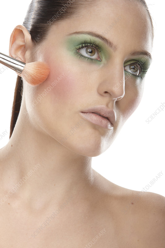 Woman applying blusher to her cheeks