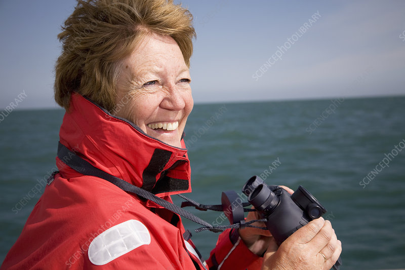 Woman with binoculars by ocean