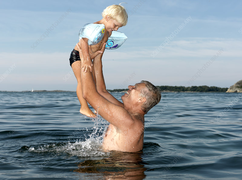 Grandfather playing with boy in water