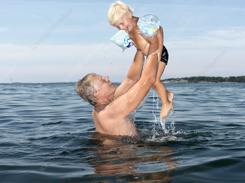 Grandfather and boy playing in water