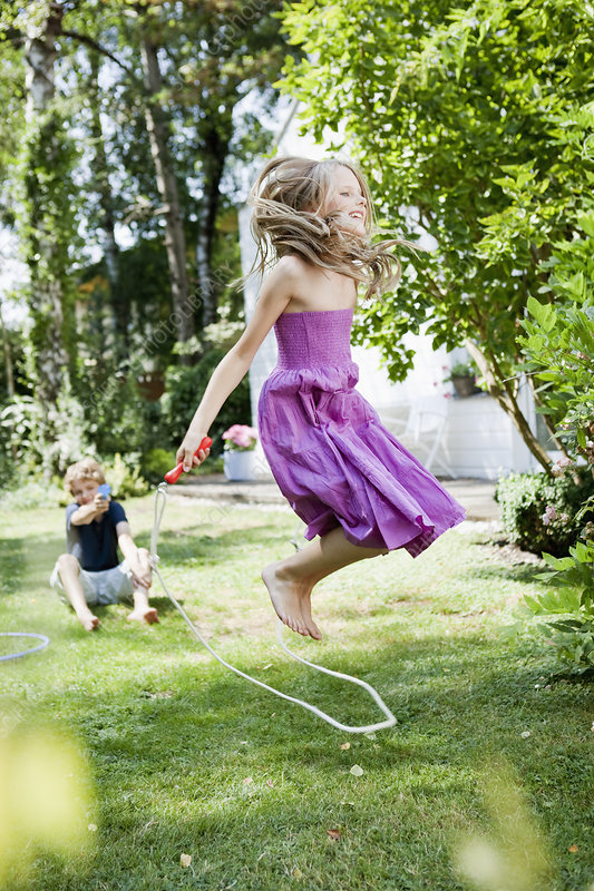 Girl jumping rope in garden
