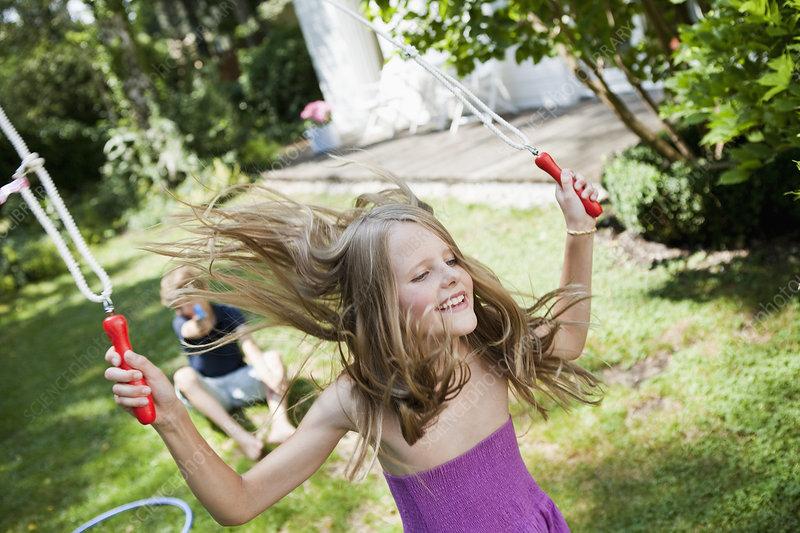 Girl jumping rope in garden