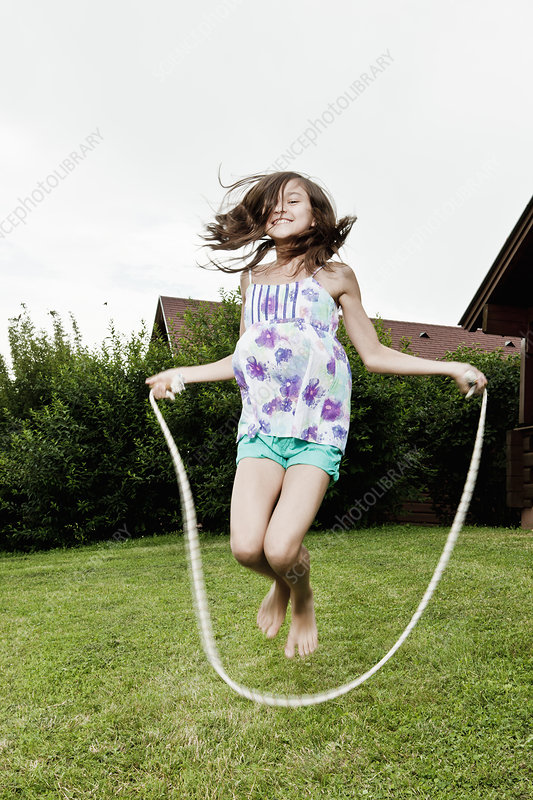 Girl skipping in garden