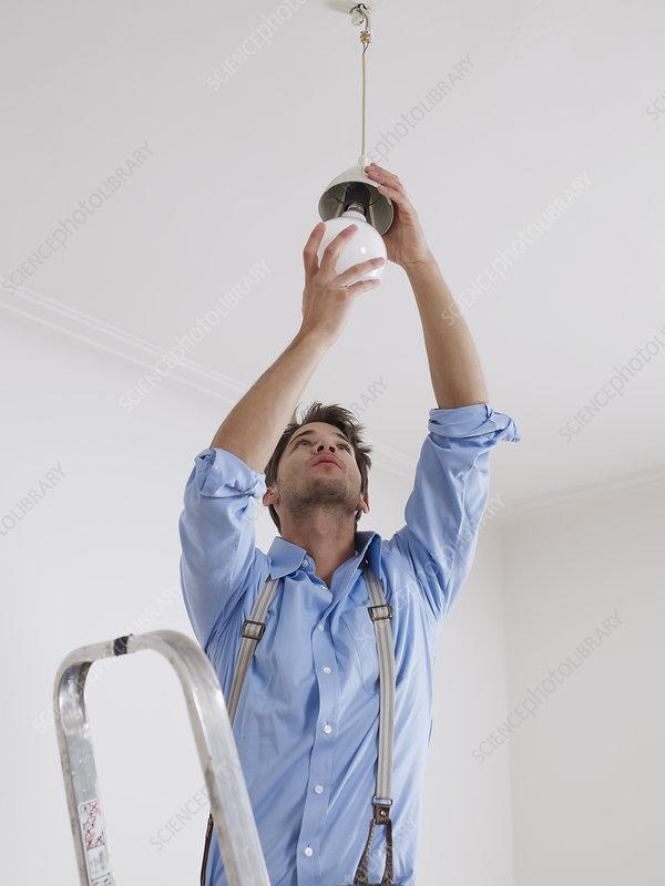 Junger Mann schraubt neue Glühbirne an