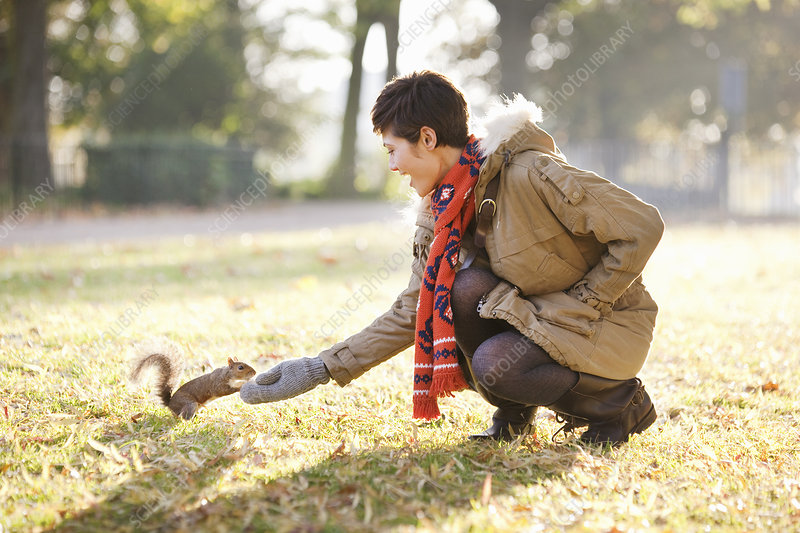 Young woman feeding a squirrel in a park