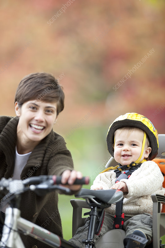 Woman and child cycle together in park