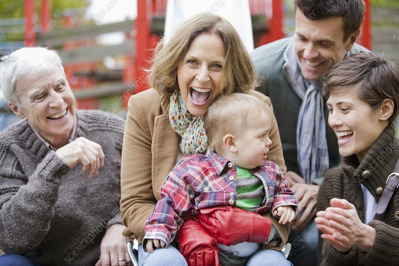Family with child laughing in the park