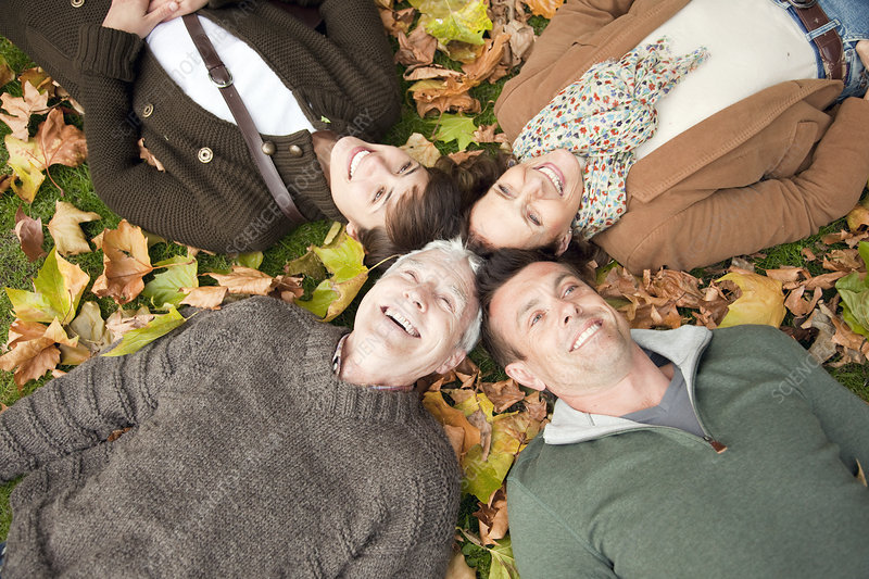 Family lying in autumn leaves in a park