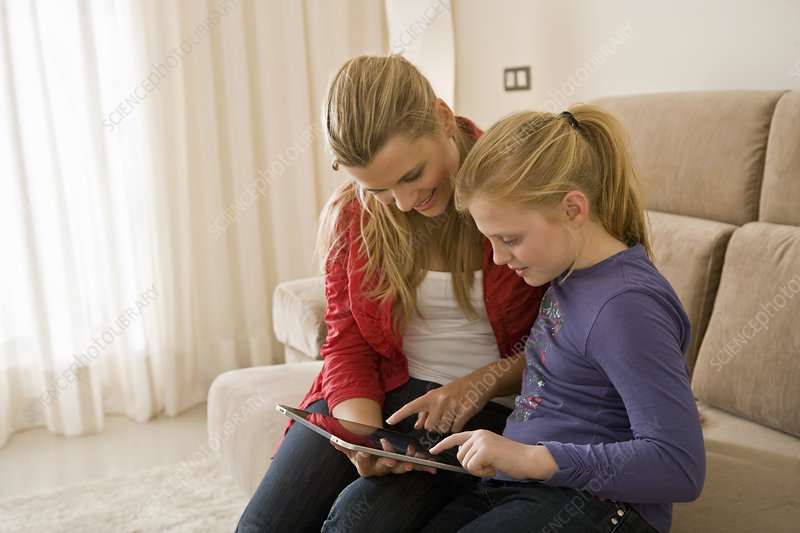Woman and girl using tablet computer