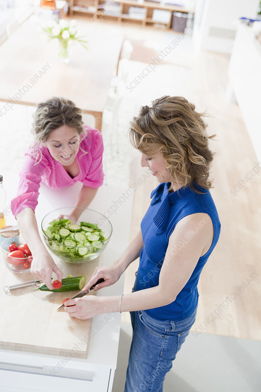 Two woman preparing salad in kitchen