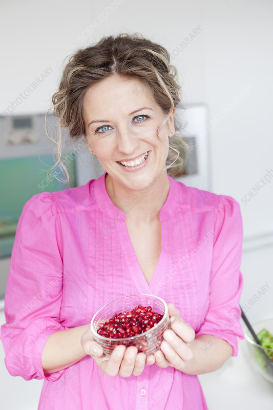 Woman holding a cup of pomegranate