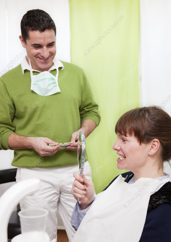 Patient examining teeth in surgery