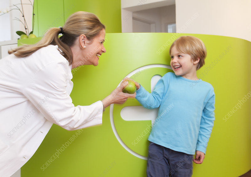 Doctor giving apple to boy
