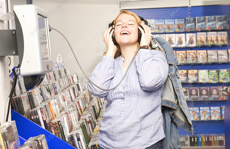 Girl enjoys listening some music in shop