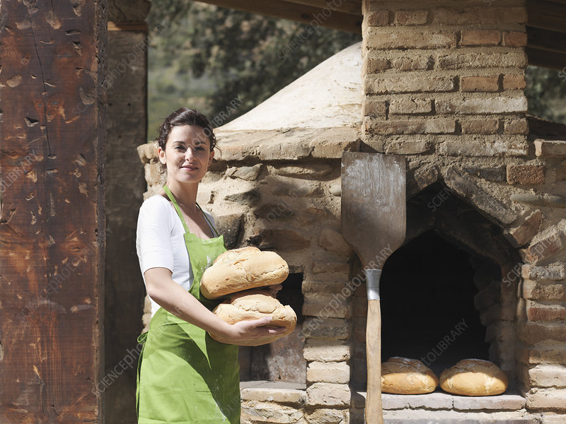 Woman holding freshly made bread loaves