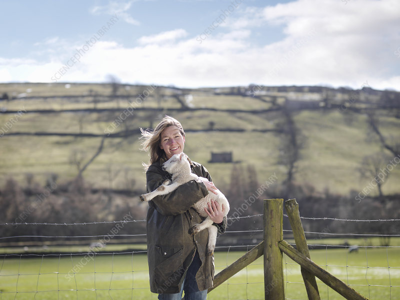Woman holding lamb in front of fence