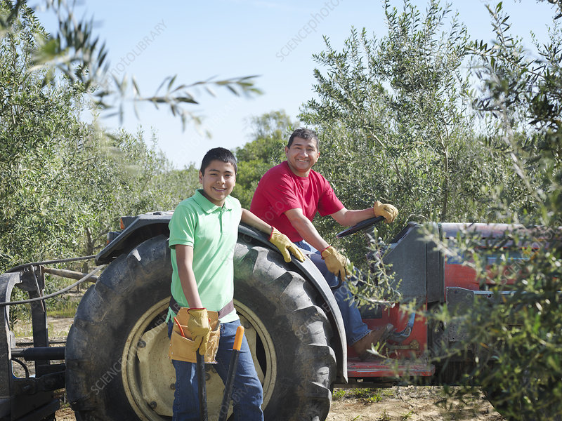 Father and son posing with tractor