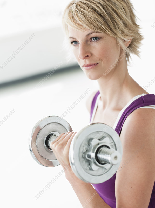 Woman with dumbbell training triceps
