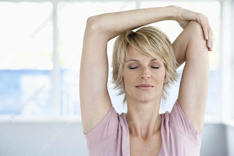 Woman stretching arms with eyes closed