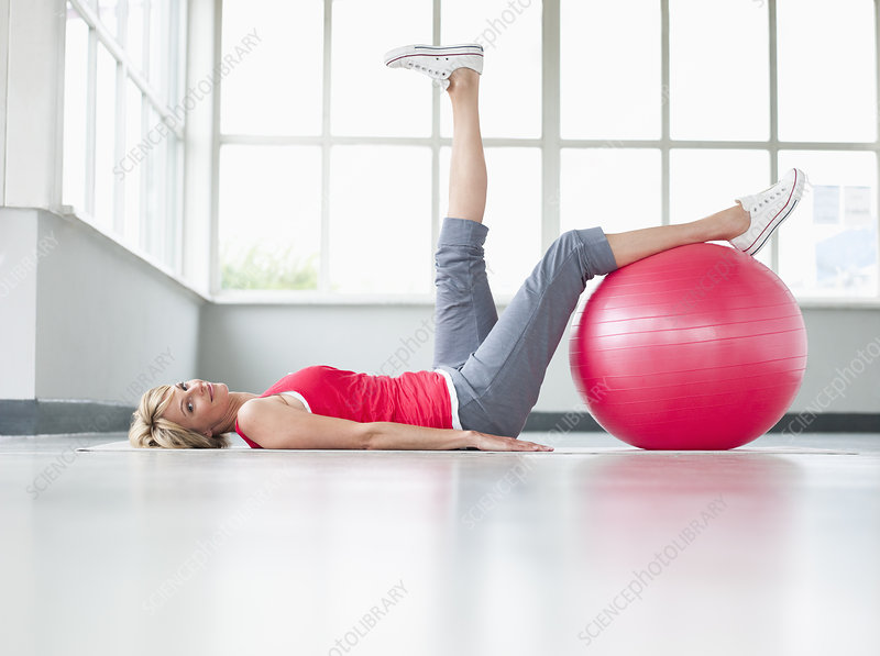 Woman doing leg exercise with gymball