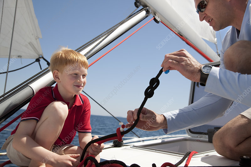 Man teaching boy knot on yacht