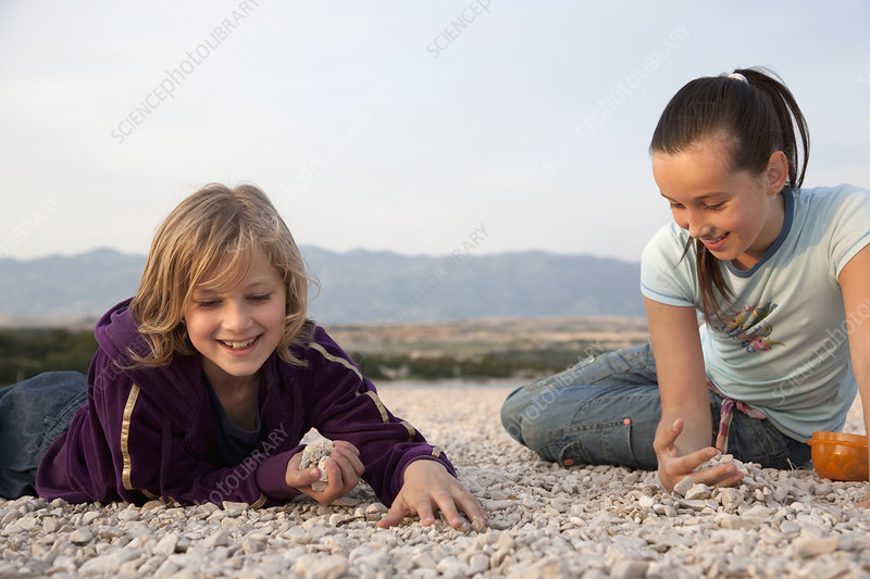 Girls collecting stones at the beach