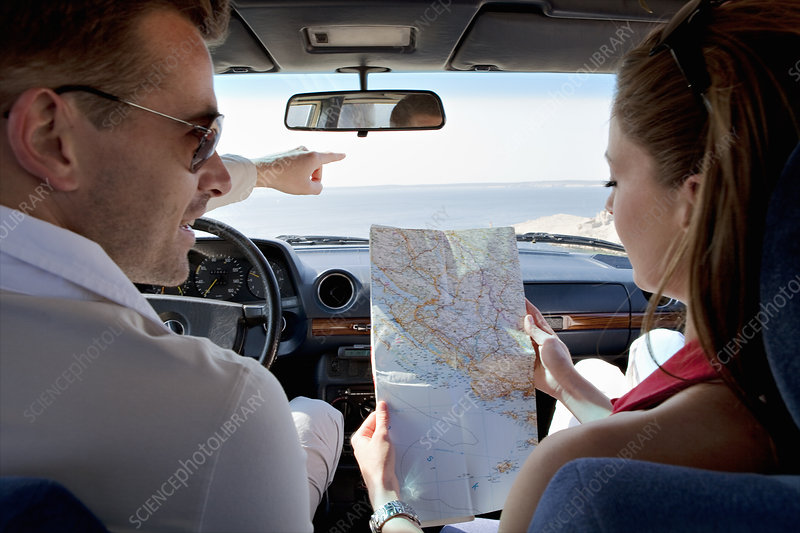 Couple looking at map in car by sea