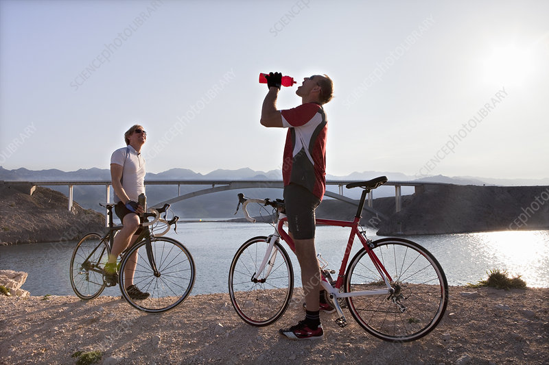 Cyclists drinking water by sea