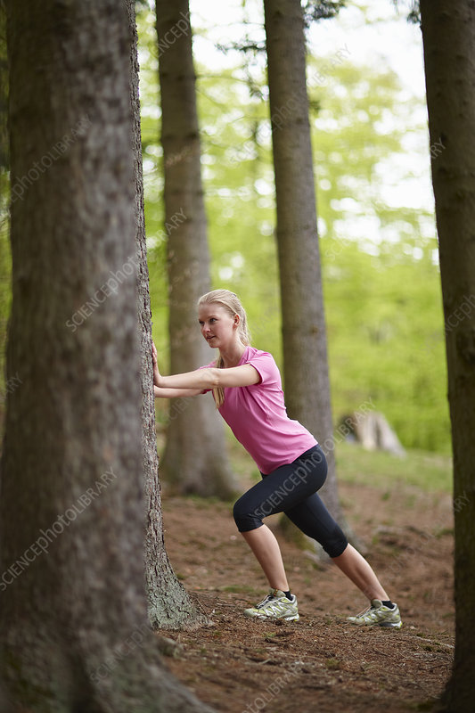 Woman running, stretching against tree
