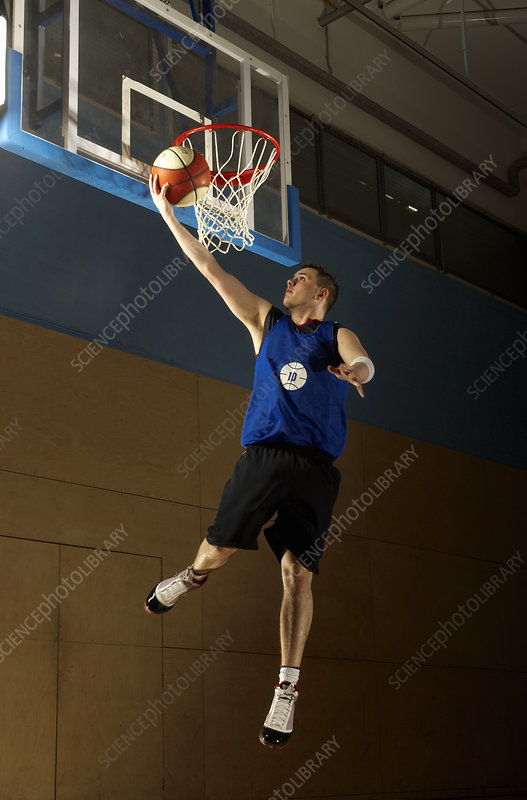 Basketball player jumping at hoop