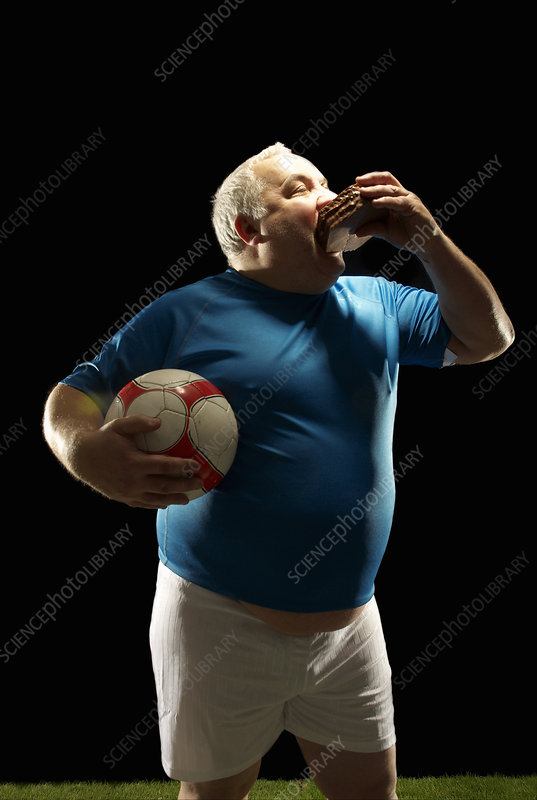 Large footballer holding ball and eating