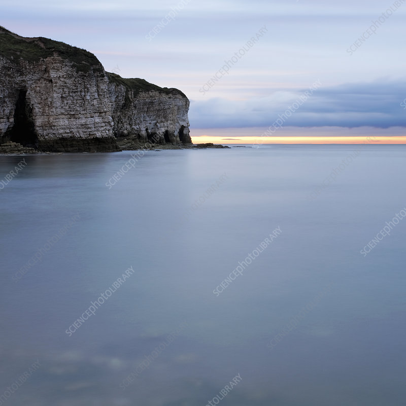 Cliffs by sea at sunset