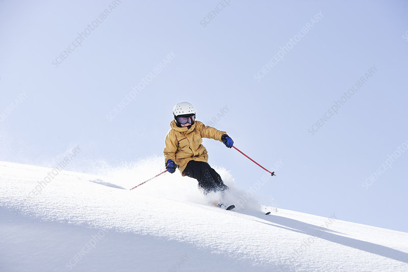 Young boy skiing through fresh powder