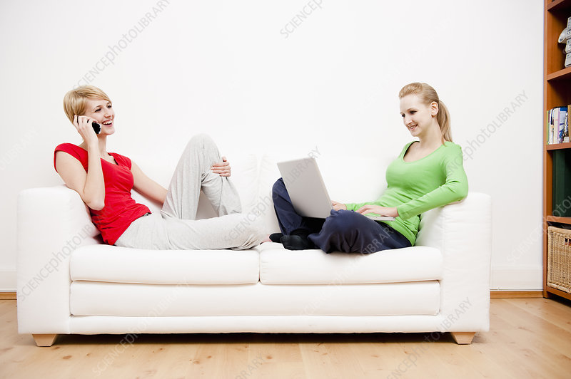 Two women using laptop and phone on sofa